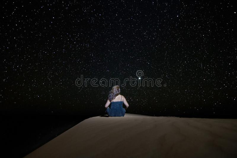 El mirar fijamente que se sienta de la mujer el cielo estrellado hacia Venus, en una duna en el desierto de Chebbi del ergio fotos de archivo libres de regalías