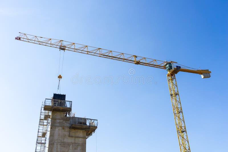 El mirar para arriba una grúa amarilla que cae del material en un edificio debajo de sitio de la construcción o de trabajo foto de archivo libre de regalías