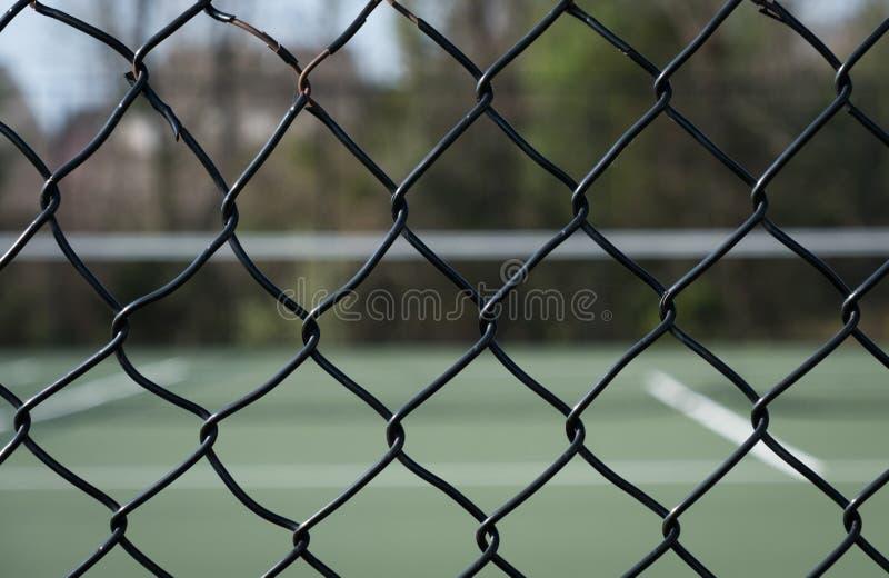 El mirar a través de la cerca el campo de tenis imagen de archivo