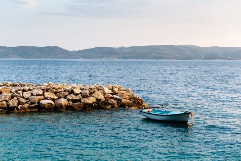 El mismo barco de pesca en agua de mar tranquilo en la puesta del sol cerca del embarcadero de piedra en Croacia, Brela foto de archivo