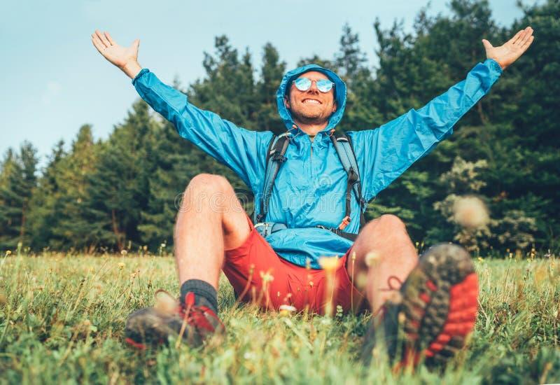 El mochilero tiene un descanso disfrutando del paisaje montañoso abierto y levantado brazos. Lleva puesto un poncho de abrigo azu fotografía de archivo