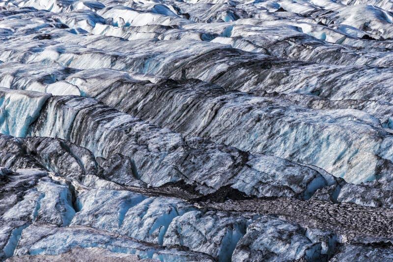 El modelo agrietado de la superficie del glaciar con los depósitos de la escoria volcánica negra, helado azul ciánico refleja est imagen de archivo libre de regalías