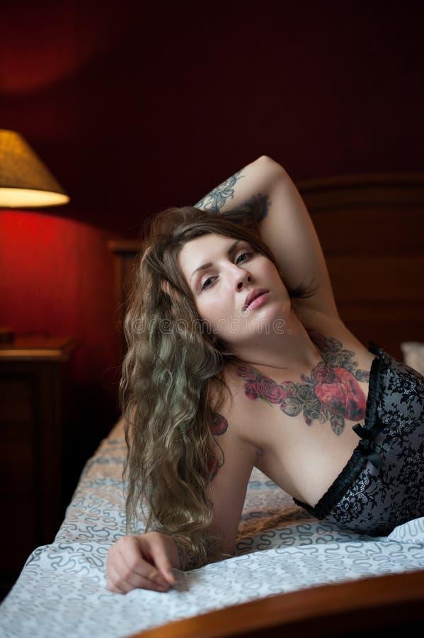 El modelo atractivo con los tatuajes góticos miente en una cama imagen de archivo libre de regalías