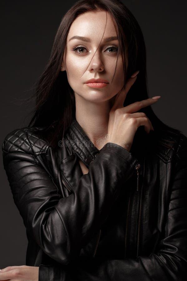 El modelo atrevido en vestido de cuero negro, estilo de la roca, oscuridad de la muchacha compone y pelo de la belleza imagen de archivo
