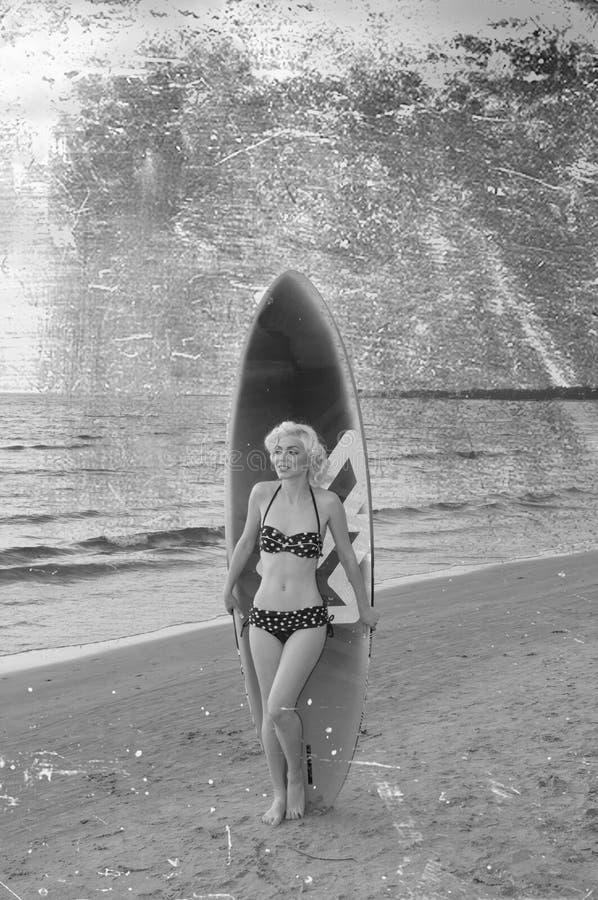 El modelo bastante rubio de la muchacha tiene gusto de Marilyn Monroe con el tablero que practica surf en una playa imagenes de archivo