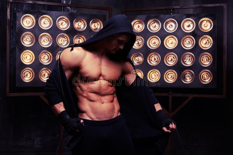El modelo de la aptitud que muestra su cuerpo fuerte atlético en estudio se enciende fotografía de archivo