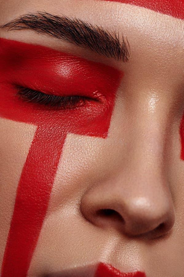 El modelo de la belleza con rojo pintó geometría en cara imagen de archivo