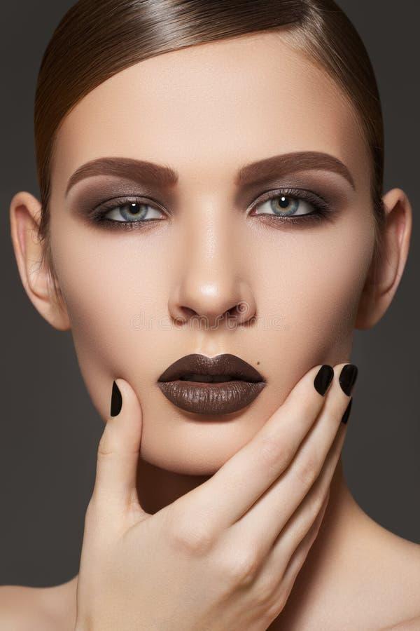 El modelo de manera con los labios construye, los ojos ahumados, clavos fotografía de archivo