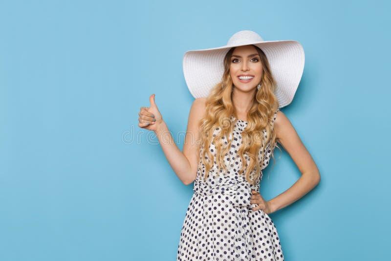 El modelo de moda elegante In Summer Dress y el sombrero de Sun está mostrando el pulgar para arriba y la sonrisa fotografía de archivo