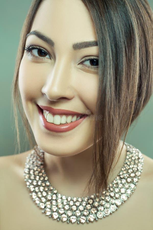 El modelo de moda hermoso con maquillaje y joyería está mirando la cámara Fondo verde, tiro del estudio Convertido de CRUDO, corr fotografía de archivo