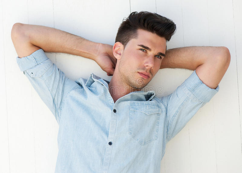 El modelo de moda masculino con los brazos aumentó detrás de la cabeza imagenes de archivo