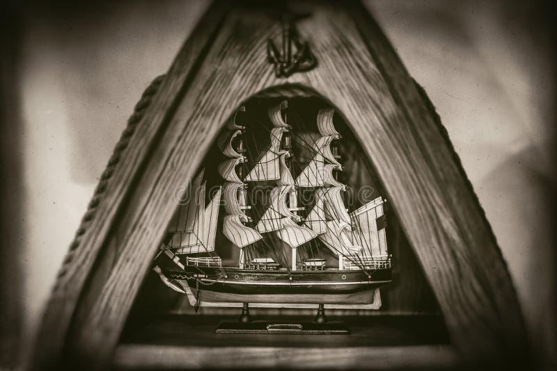 El modelo de nave alto en el marco de madera triangular, ancla, cuerda, aislada en fondo borroso, se descoloró en fotografía del  foto de archivo libre de regalías
