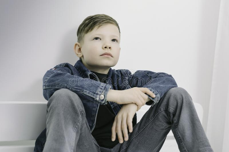 El modelo del muchacho, delante del fondo blanco, chaqueta de los vaqueros, suelta mirada, fotos de archivo