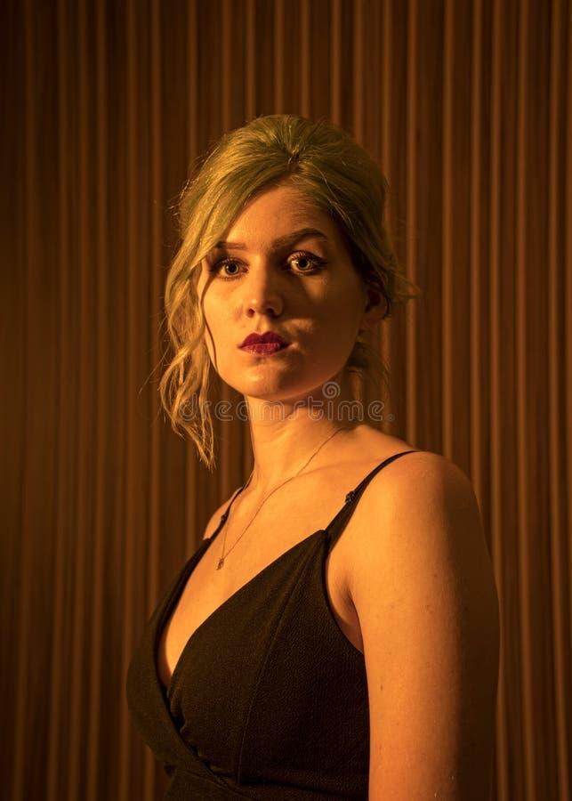 El modelo femenino caucásico, edad 22, azul teñió el pelo, labios rojos, top de tiras del negro, filtro anaranjado Principal y ho foto de archivo