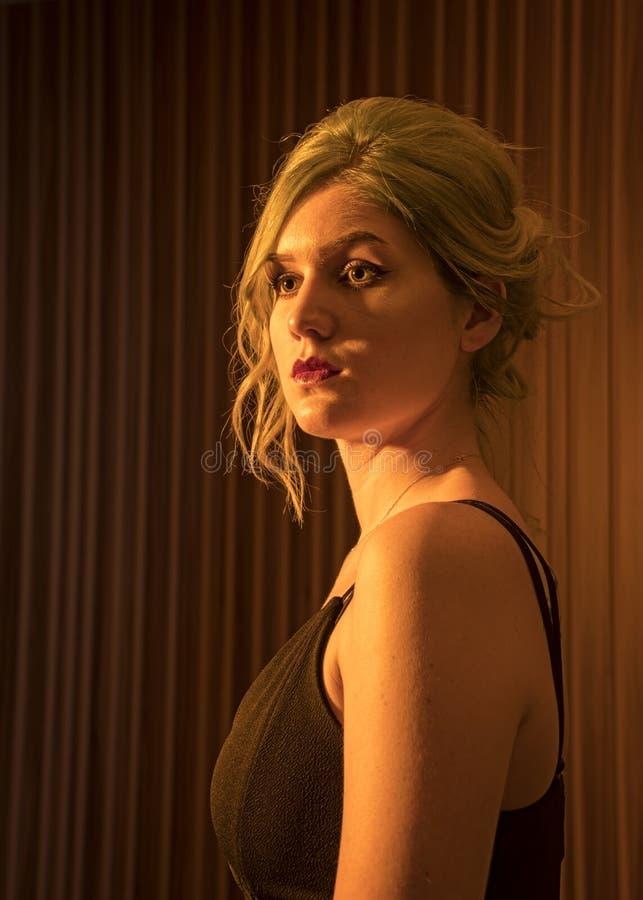 El modelo femenino caucásico, edad 22, azul teñió el pelo, labios rojos, top de tiras del negro, filtro anaranjado Principal y ho fotografía de archivo