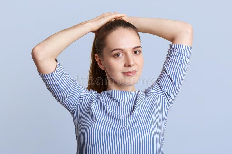 El modelo femenino joven de mirada agradable hace la cola de potro, lleva la blusa elegante rayada, presenta contra fondo azul en imagenes de archivo
