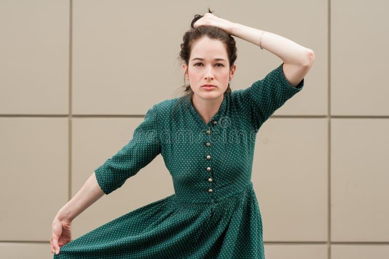 El modelo femenino que lleva a cabo su verde del pelo y del verano se viste imagen de archivo libre de regalías