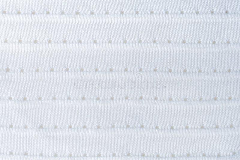 El modelo geométrico en blanco hizo punto la tela con las rayas y los agujeros horizontales imagen de archivo