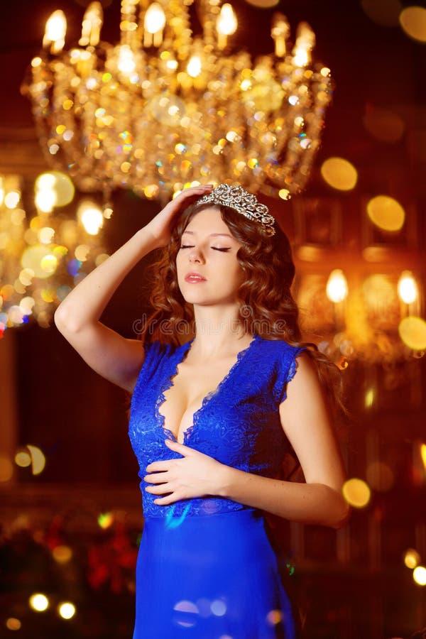 El modelo hermoso de la muchacha celebra la Navidad o el Año Nuevo en un interior clásico, cerca de un árbol del Año Nuevo, picea imagenes de archivo