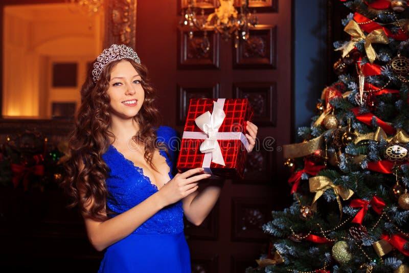 El modelo hermoso de la muchacha celebra la Navidad o el Año Nuevo en un interior clásico, cerca de un árbol del Año Nuevo, picea fotografía de archivo libre de regalías