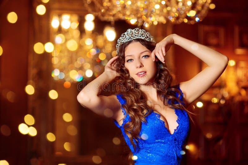 El modelo hermoso de la muchacha celebra la Navidad o el Año Nuevo en un interior clásico, cerca de un árbol del Año Nuevo, picea foto de archivo libre de regalías
