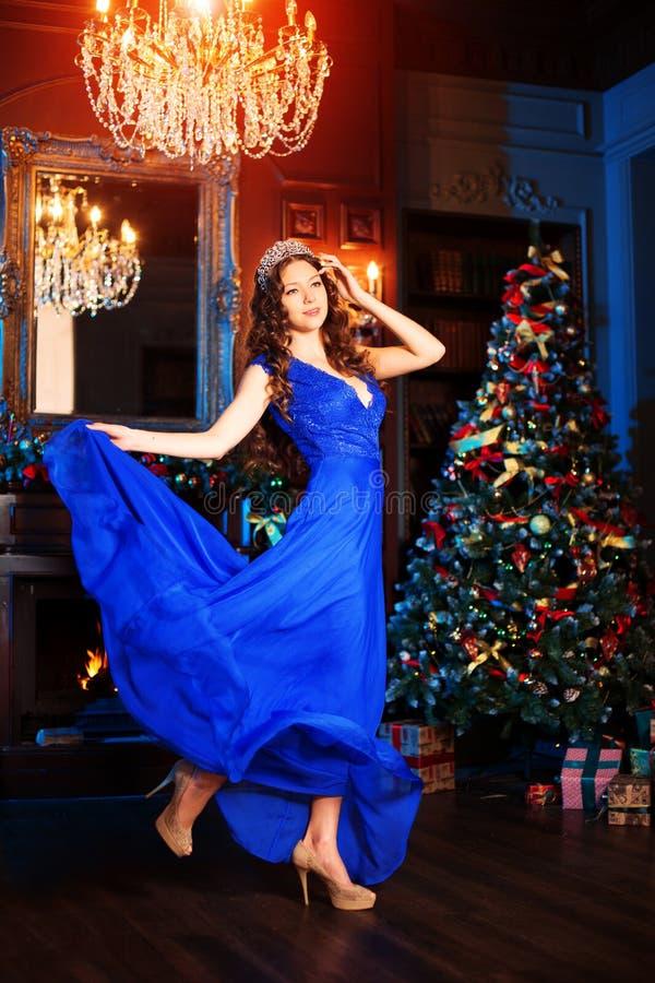 El modelo hermoso de la muchacha celebra la Navidad o el Año Nuevo en un interior clásico, cerca de un árbol del Año Nuevo, picea imágenes de archivo libres de regalías