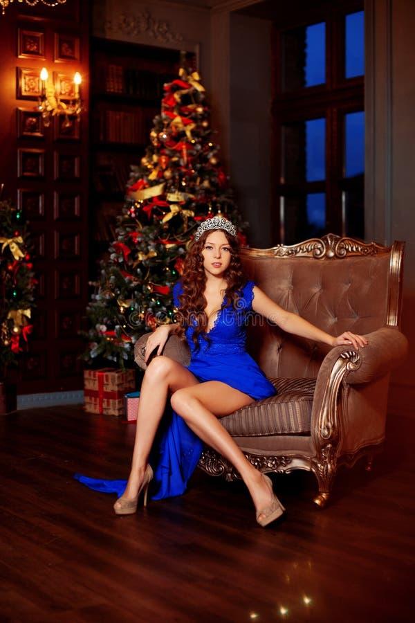 El modelo hermoso de la muchacha celebra la Navidad o el Año Nuevo en un interior clásico, cerca de un árbol del Año Nuevo, picea foto de archivo
