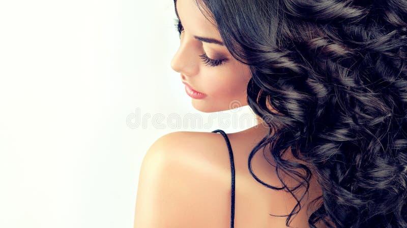 El modelo hermoso de la muchacha del retrato con negro largo encrespó el pelo imagen de archivo