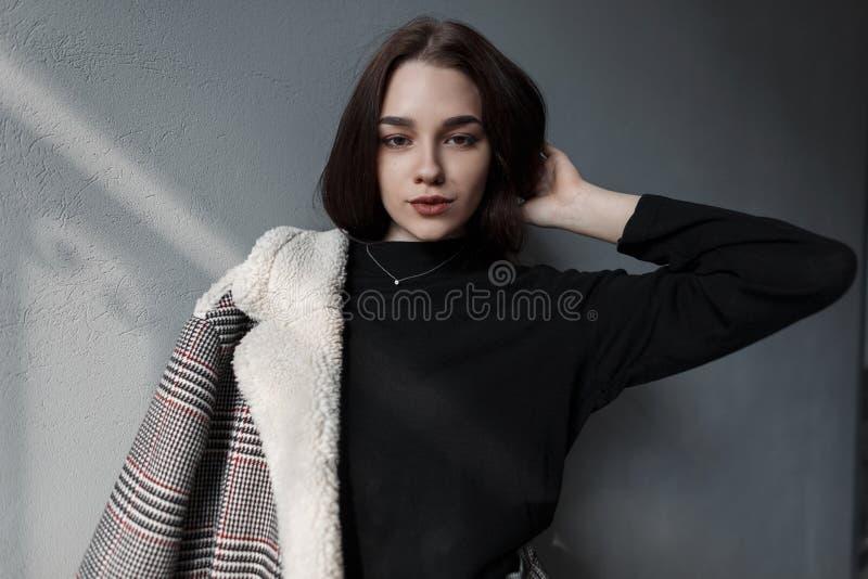 El modelo hermoso de la mujer joven con maquillaje natural con los ojos hermosos en ropa de moda de la primavera está descansando imagen de archivo libre de regalías