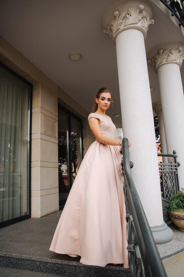 El modelo joven con el gran vestido de noche hace una pausa el restaurante La muchacha morena tiene estilo y maquillaje hermosos  foto de archivo libre de regalías