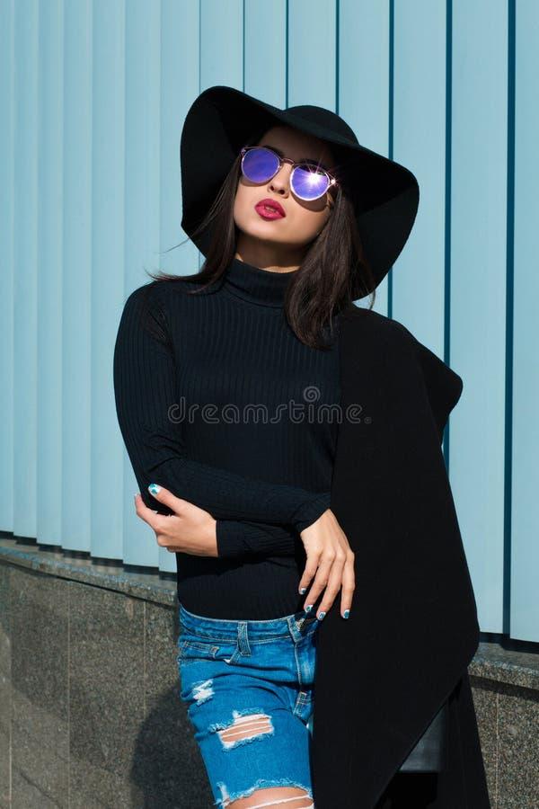 El modelo joven de lujo lleva la capa de moda, vaqueros rasgados y el sombrero Woma fotografía de archivo