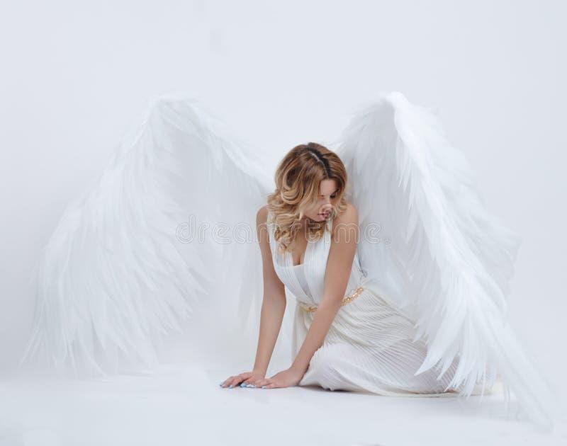 El modelo joven hermoso con ángel grande se va volando sentarse en el estudio imagenes de archivo