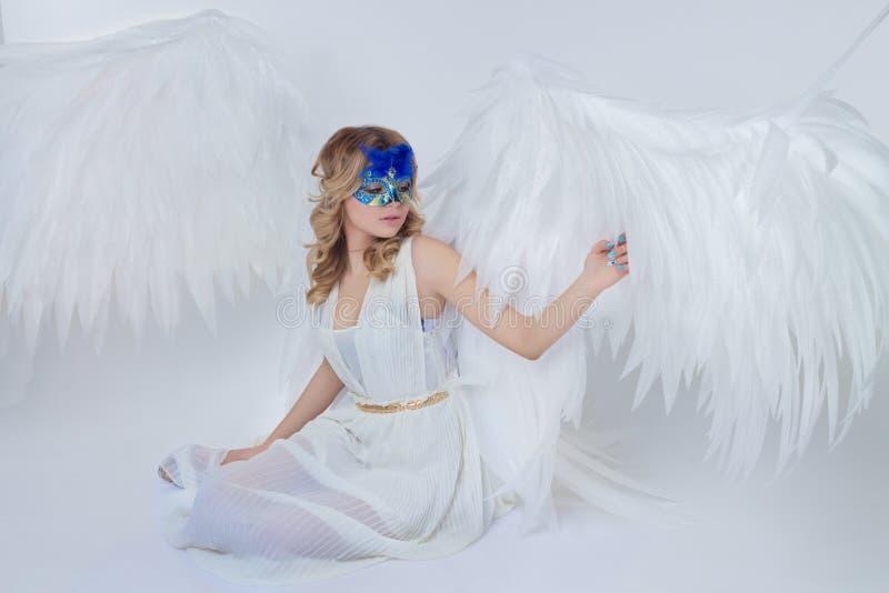 El modelo joven hermoso con ángel grande se va volando sentarse en el estudio foto de archivo libre de regalías