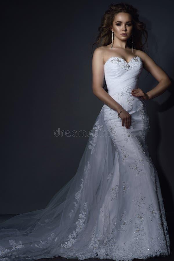 El modelo joven hermoso con perfecto compone y pelo que sopla que lleva el vestido de boda blanco del cordón de la sirena lujosa  fotografía de archivo libre de regalías