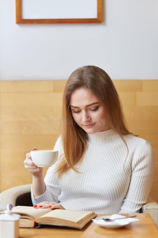 El modelo joven plantea la sentada en el café, libro interesante de la lectura, sosteniendo la taza de café en mano derecha, cent foto de archivo libre de regalías