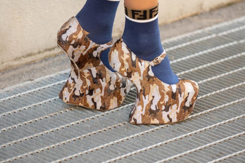 El modelo lleva un par de zapatos del camuflaje del talón y de calcetines azules de Fendi imagenes de archivo