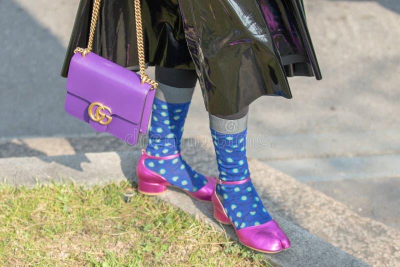 El modelo lleva un par de zapatos púrpuras del talón y de un bolso púrpura fotografía de archivo libre de regalías