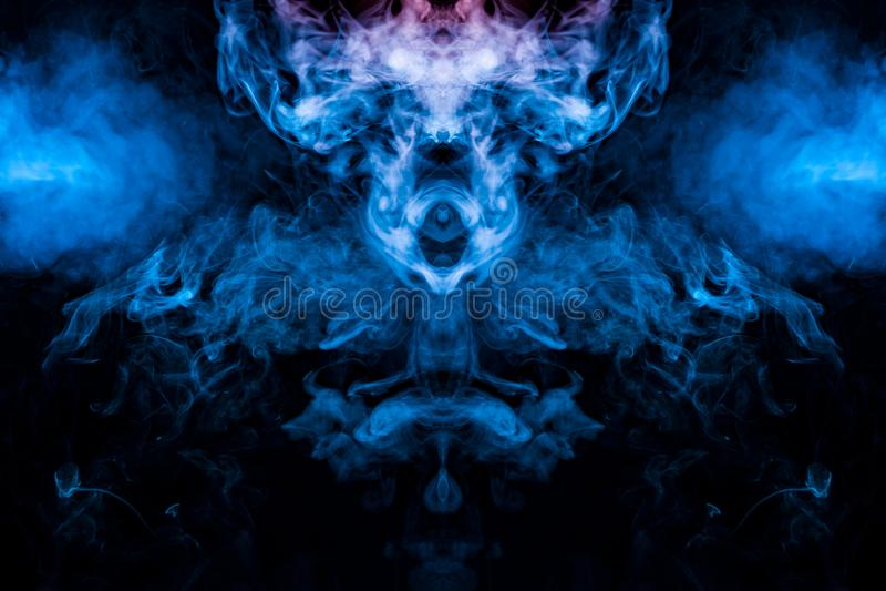 El modelo místico y misterioso de evaporar humo azul en un fondo negro es similar en diseño a una cabeza extranjera y a los ojos imagen de archivo libre de regalías