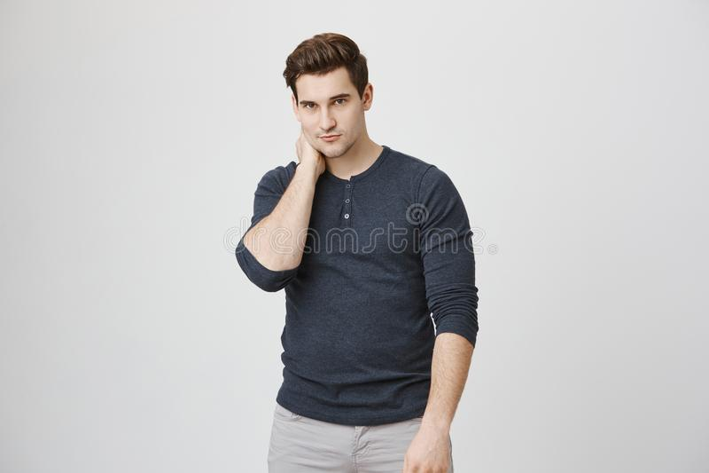 El modelo masculino atlético y caliente en ropa casual mira la cámara mientras que se sostiene el cuello con una mano, aislada so foto de archivo