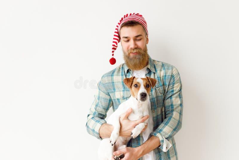 El modelo masculino barbudo positivo lleva el sombrero festivo y la camisa a cuadros, sostiene su animal doméstico preferido, sob fotos de archivo