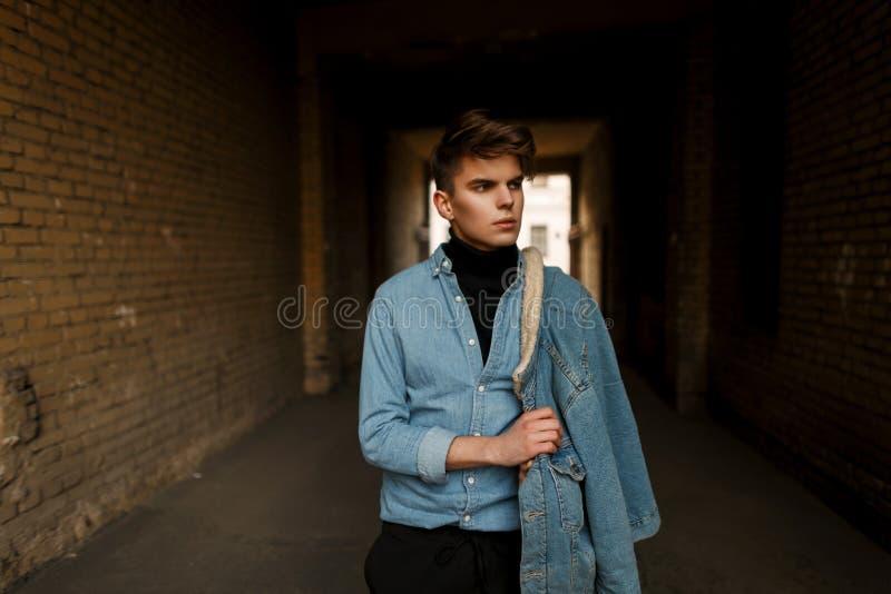 El modelo masculino joven hermoso en una camisa del dril de algodón y un dril de algodón se coloca fotos de archivo libres de regalías
