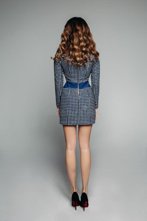 El modelo moreno en oficina comprobó el vestido y los tacones altos foto de archivo