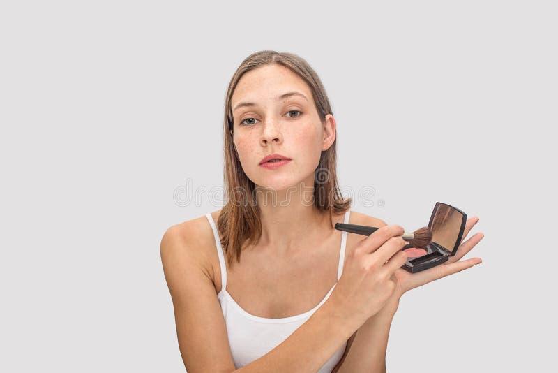 El modelo pecoso joven presenta en cámara Ella lleva a cabo el pallete de sombras de ojos y utiliza el cepillo para ése Miradas m fotos de archivo