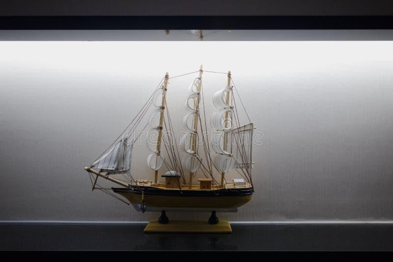 El modelo Sailboat Frigate Sitting en la decoración elegante blanca negra de las luces del estante de exhibición se centró imagen de archivo