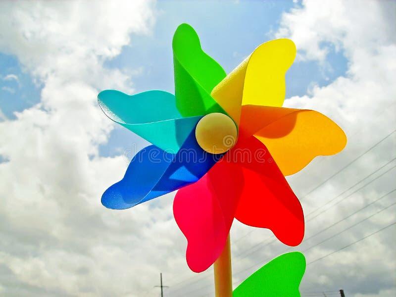 El molinillo de viento colorido del arco iris delante de una nube hermosa llenó el cielo foto de archivo libre de regalías