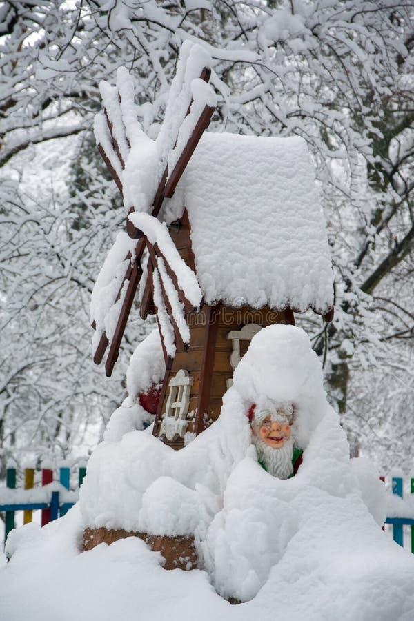 El molino de viento decorativo y el gnomo cubiertos con nieve fresca en invierno parquean foto de archivo libre de regalías