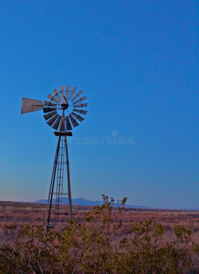 El molino de viento solitario viejo todavía se sienta en la oscuridad con la montaña en el fondo fotos de archivo