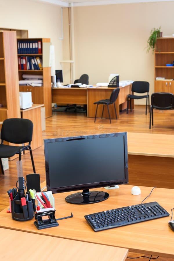 El monitor de computadora negro del lcd está apagado en sitio vacío de la oficina después del final del día laborable fotografía de archivo