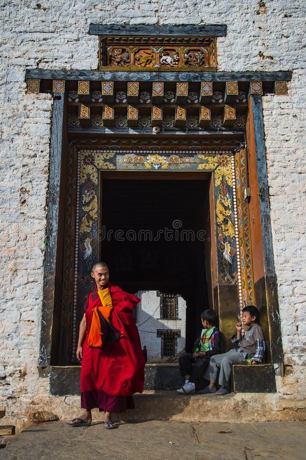 El monje budista sostiene su libro del mantra y sale de la puerta de Dzong, Trashigang Dzong, Bhután del este imagen de archivo
