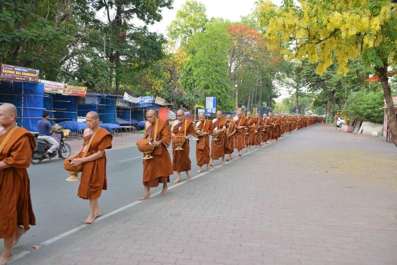 El monje budista Walking para recibe la comida en Buda Gaya, la India imagen de archivo